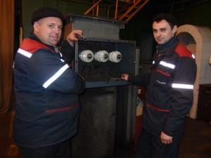 Электромонтеры Игорь Гурий и Иван Кучук ремонтируют понижающий трансформатор.
